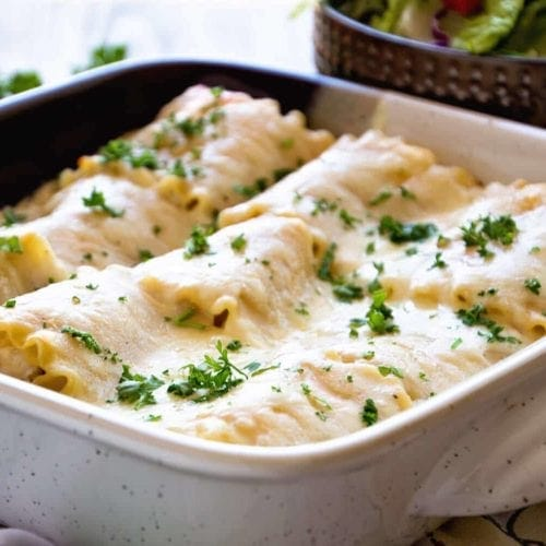 A square baking dish of chicken alfredo roll ups topped with fresh parsley