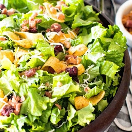 Lettuce Frito Salad in a wood bowl next to a grey and white striped towel with a metal tongs