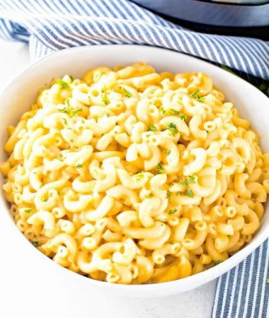 Pressure cooker macaroni and cheese in a white bowl in front of a pressure cooker