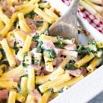Spinach Ham Pasta Casserole in a white baking dish with a wood spoon in it