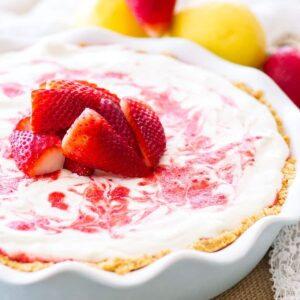 A strawberry lemon icebox pie on a burlap place mat with strawberries and lemons