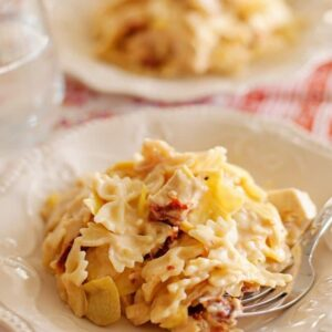 Two white plates of sun dried tomato and artichoke pasta with forks
