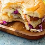 Fish sandiwch with garlic aioli coleslaw on cutting board with a bite missing