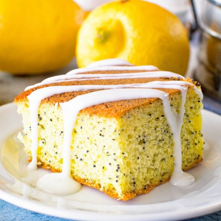 Poppy seed cake piece on a white plate with lemons and eggs in the background
