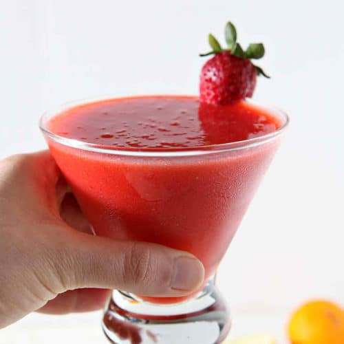 A woman holds a Strawberry Virgin Margarita in her hand before drinking.