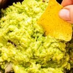 Hand holding a tortilla chip and dipping it into guacamole