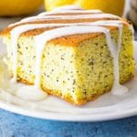 Piece of lemon poppy seed cake with icing on a white plate