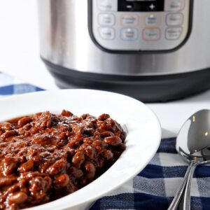 Instant Pot Baked Beans are served in a white bowl in front of an Instant Pot