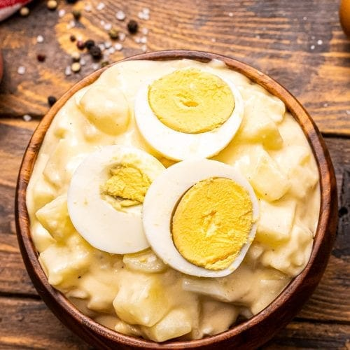 Overhead photo of brown bowl with potato salad and sliced eggs on top