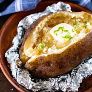 Baked Potato with butter in foil on a wood plate