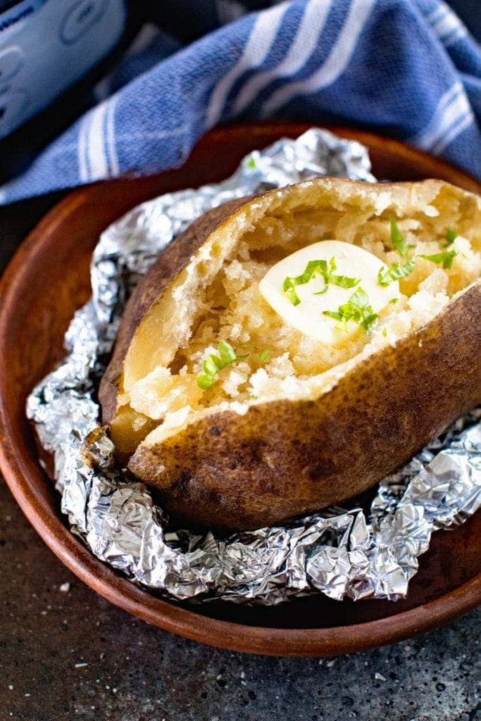 Close up image of a sliced open baked potato topped with butter on a scrunched piece of aluminum foil. A blue and white striped cloth napkin in background.