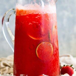 Glass pitcher of strawberry lemonade margarita sitting in ice