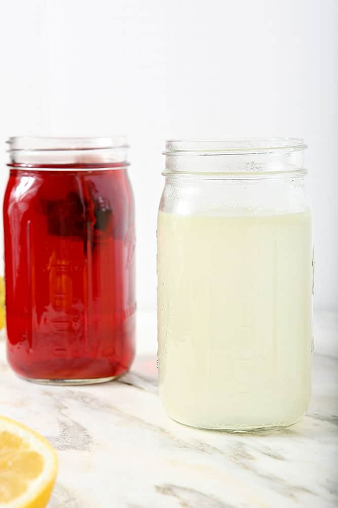 A mason jar full of homemade lemonade and a mason jar full of homemade unsweetened tea sit side by site on a marble background