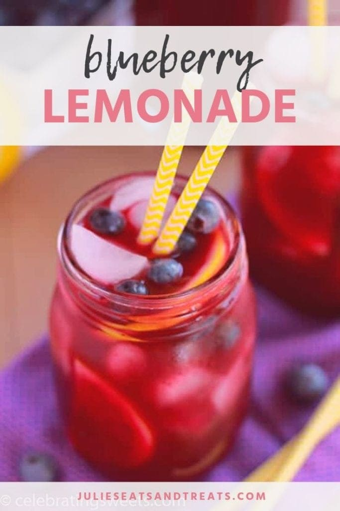 Blueberry lemonade in a mason jar with blueberries, a lemon wedge, and two yellow straws