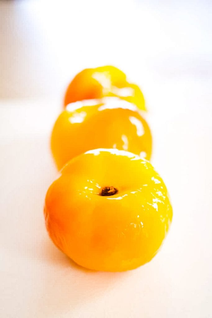 Peeled peaches lined up in a row on white background