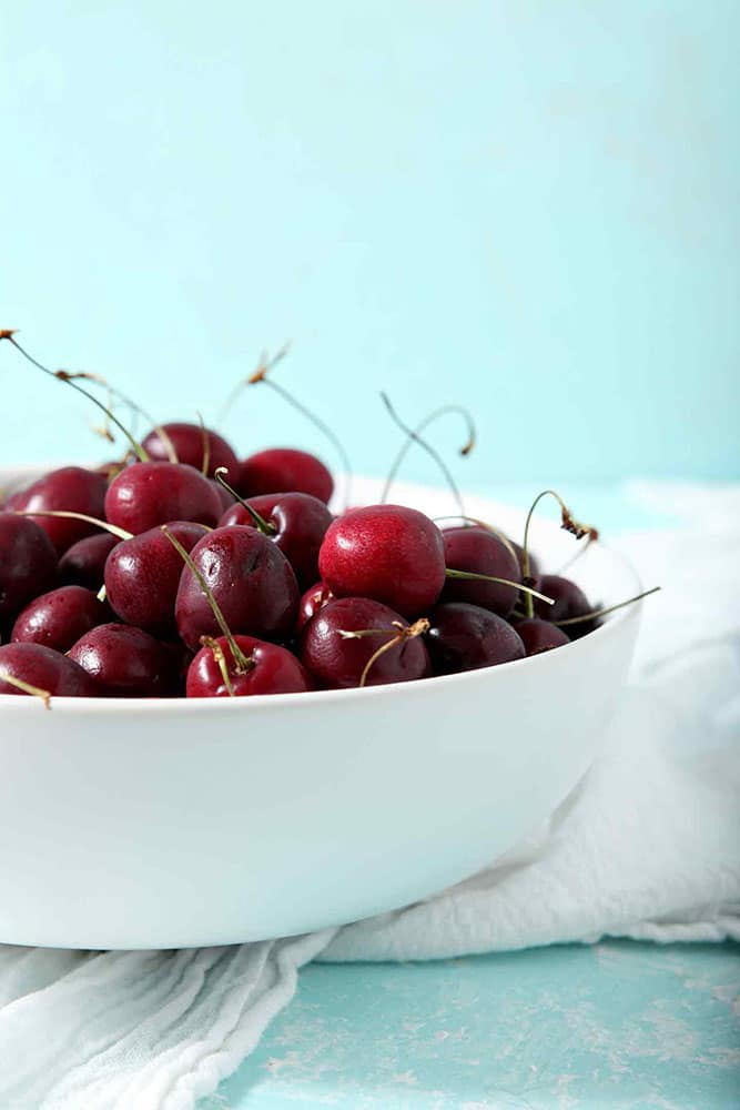 Cherries sit in a white bowl on a turquoise background