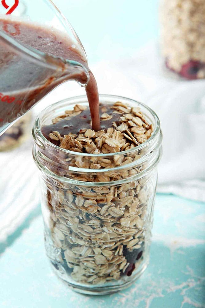 How to make overnight oats - A mixture of cashew milk, maple syrup and cherry puree are poured in top of rolled oats