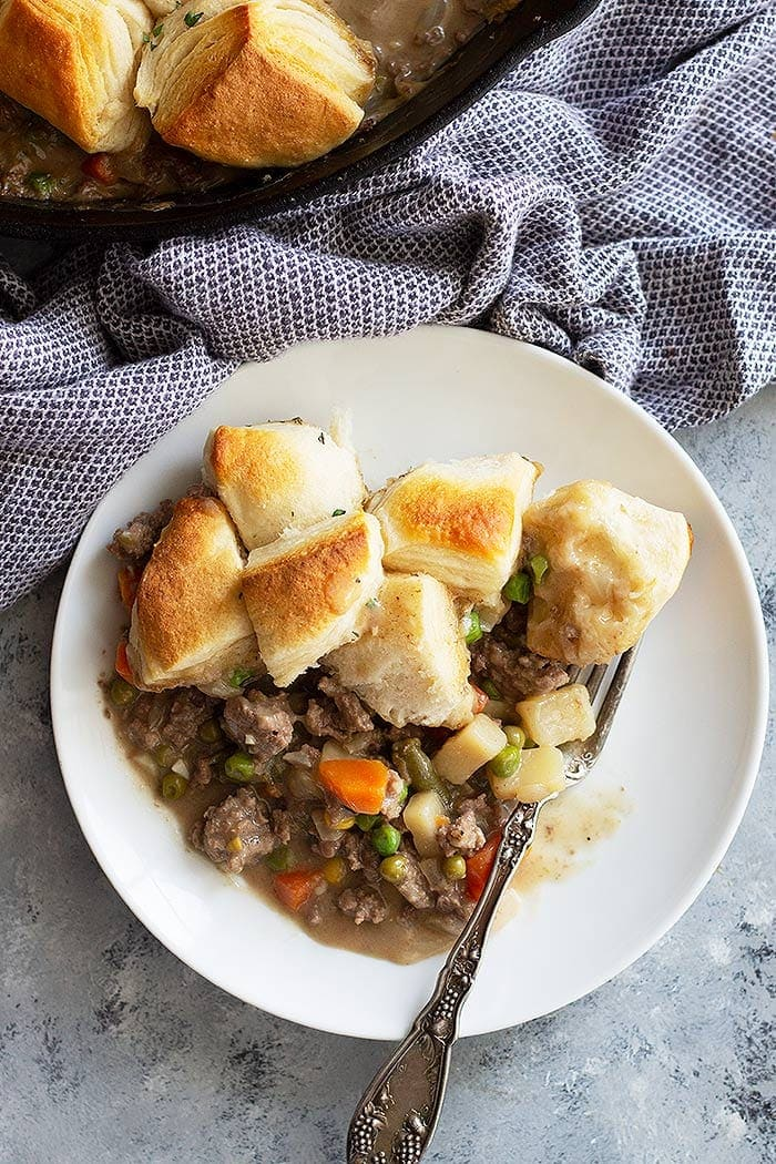 Beef Pot pie in a white bowl piled with biscuits!