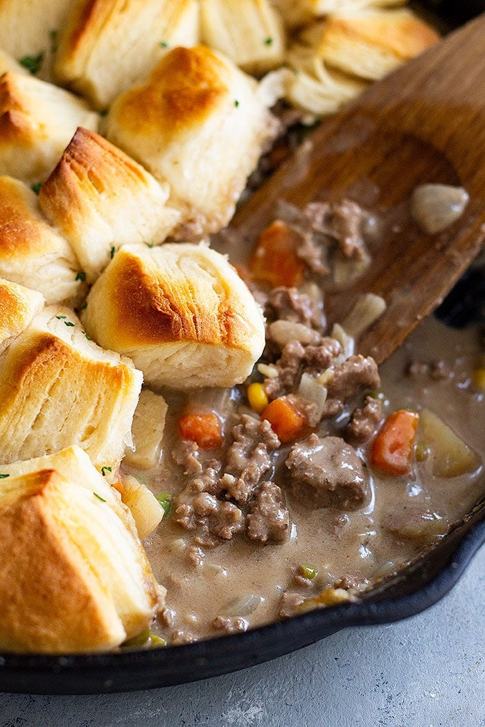 Ground beef pot pie in a skillet with biscuits. A wooden spoon is mixing the Beef Pot Pie