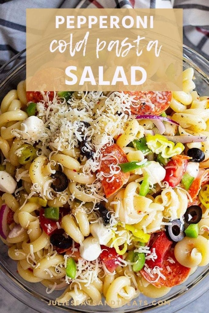 Pepperoni cold pasta salad topped with shredded cheese in a glass bowl