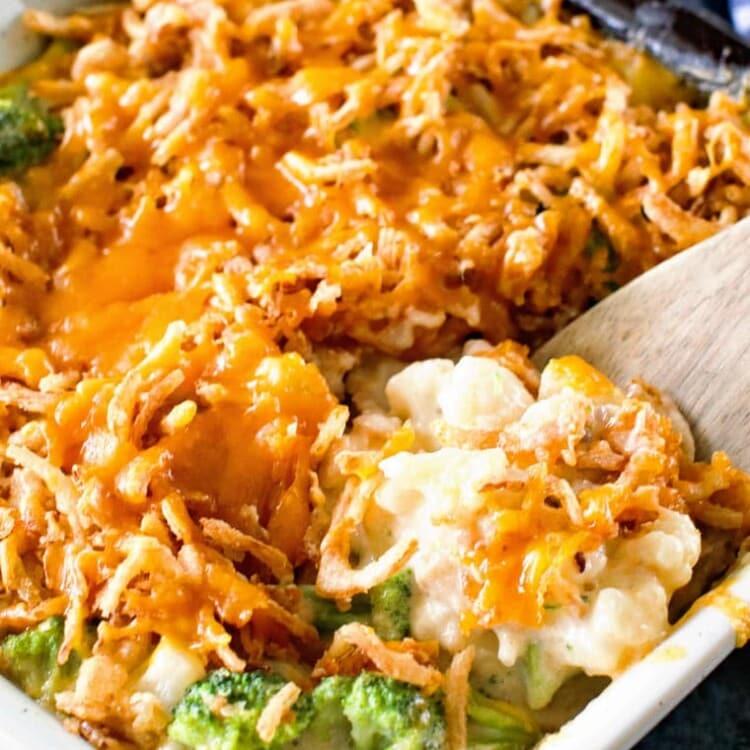 broccoli cauliflower cheese casserole with spoon in casserole dish