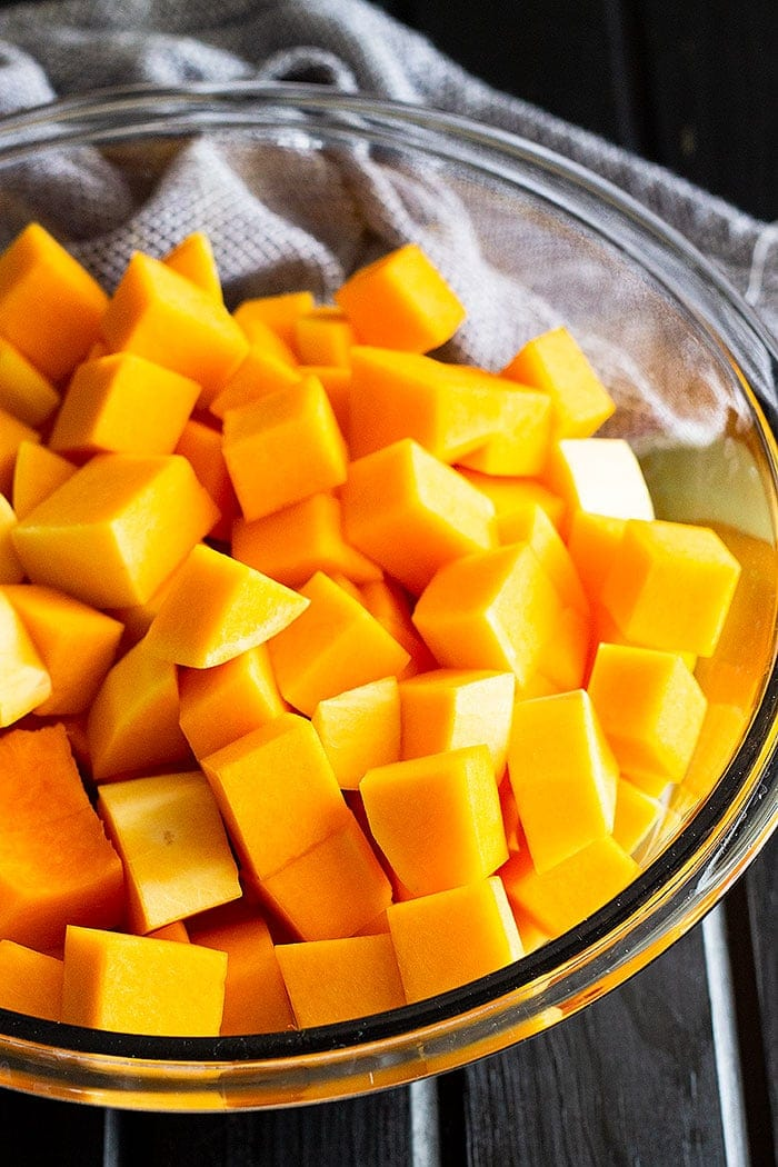 Directions how to roast butternut squash - diced squash in a clear glass bowl.