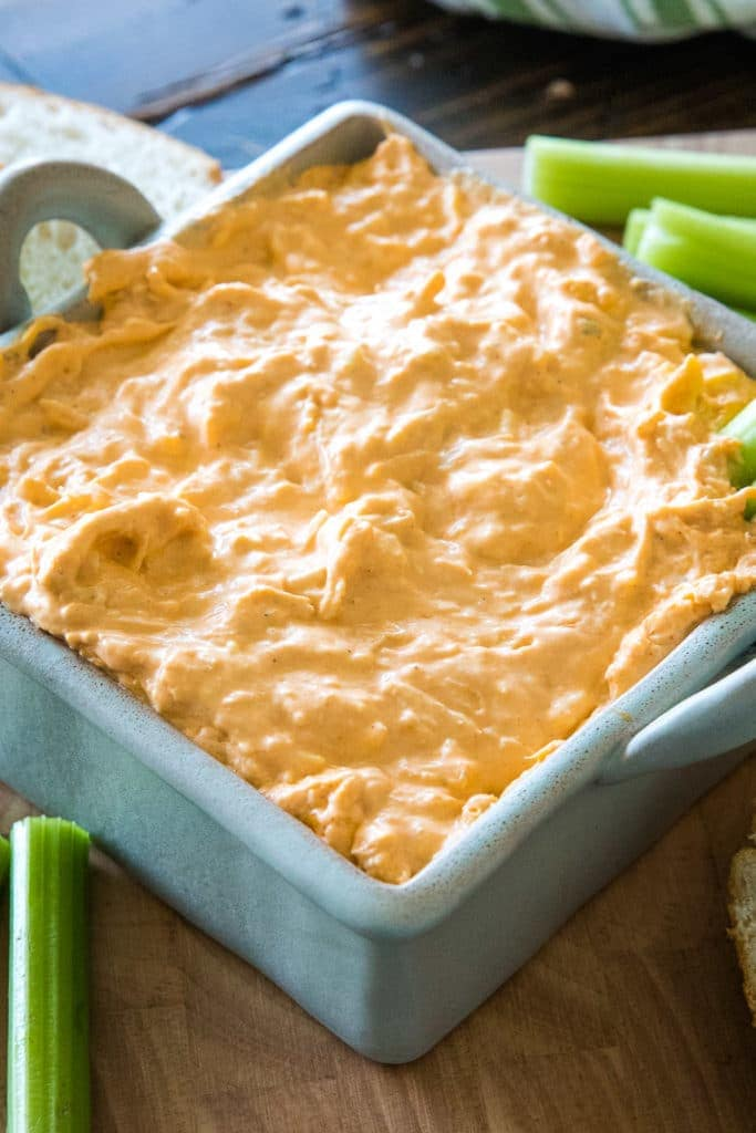 Gray square dish with prepared buffalo chicken dip and celery on the sides