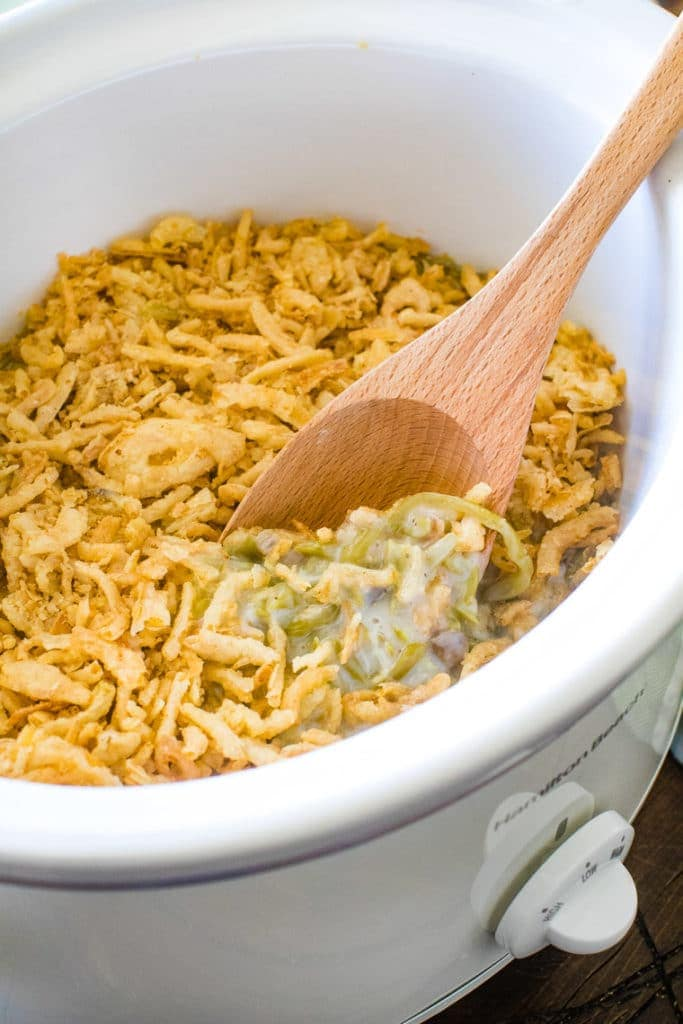 White crockpot with green bean casserole in it and a wooden spoon sitting in it.