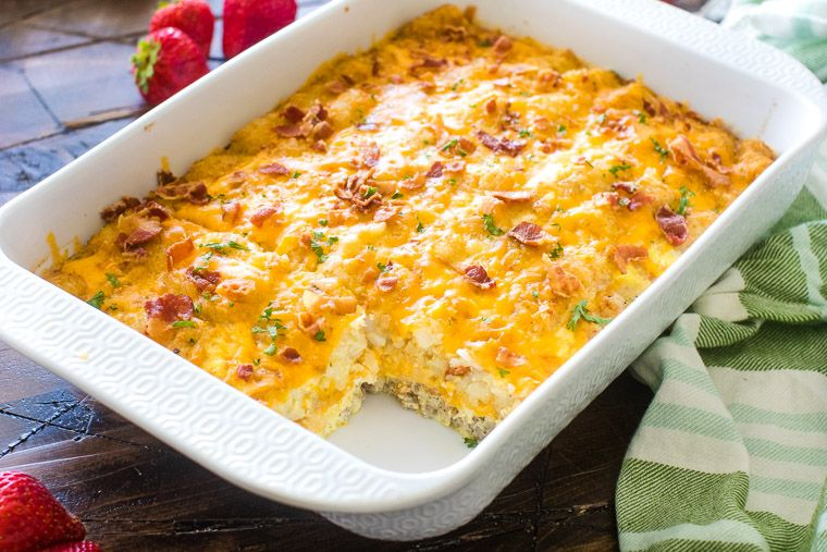 Tater Tot Sausage Breakfast Casserole in white baking dish. There's a slice missing from Breakfast Tater Tot Casserole looks like someone got hungry!
