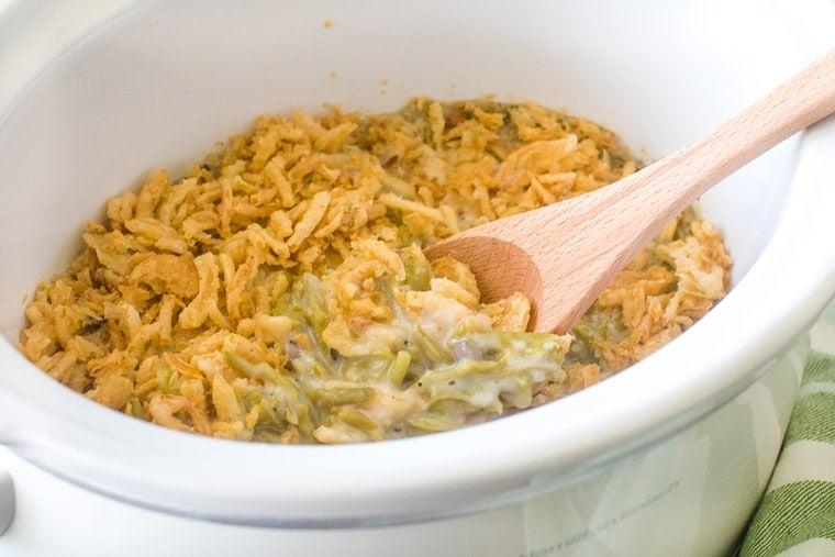 Spoon in green bean casserole in a crockpot