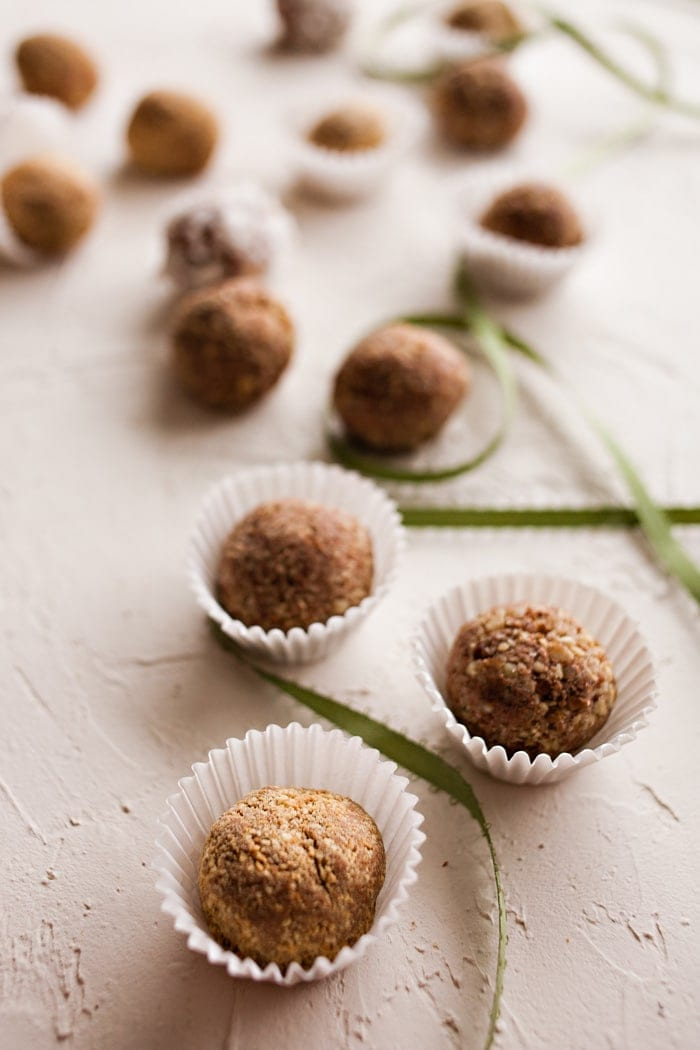 Soft chocolate balls are rolled in nuts or cookie crumbs in white candy wrappers.