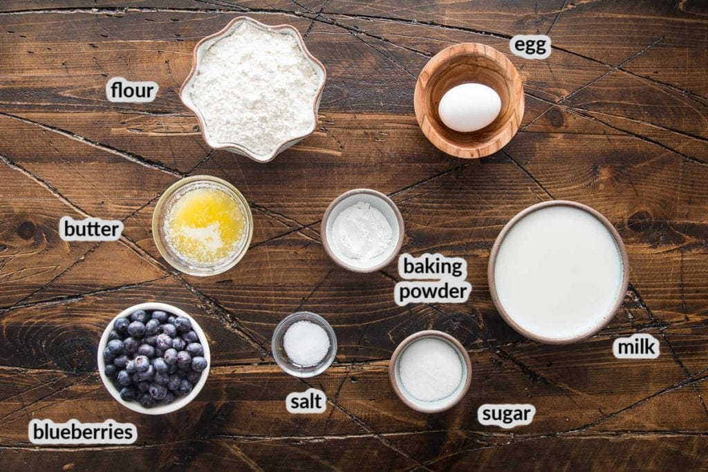 Overhead image showing ingredients to make blueberry pancakes in bowls on wood background