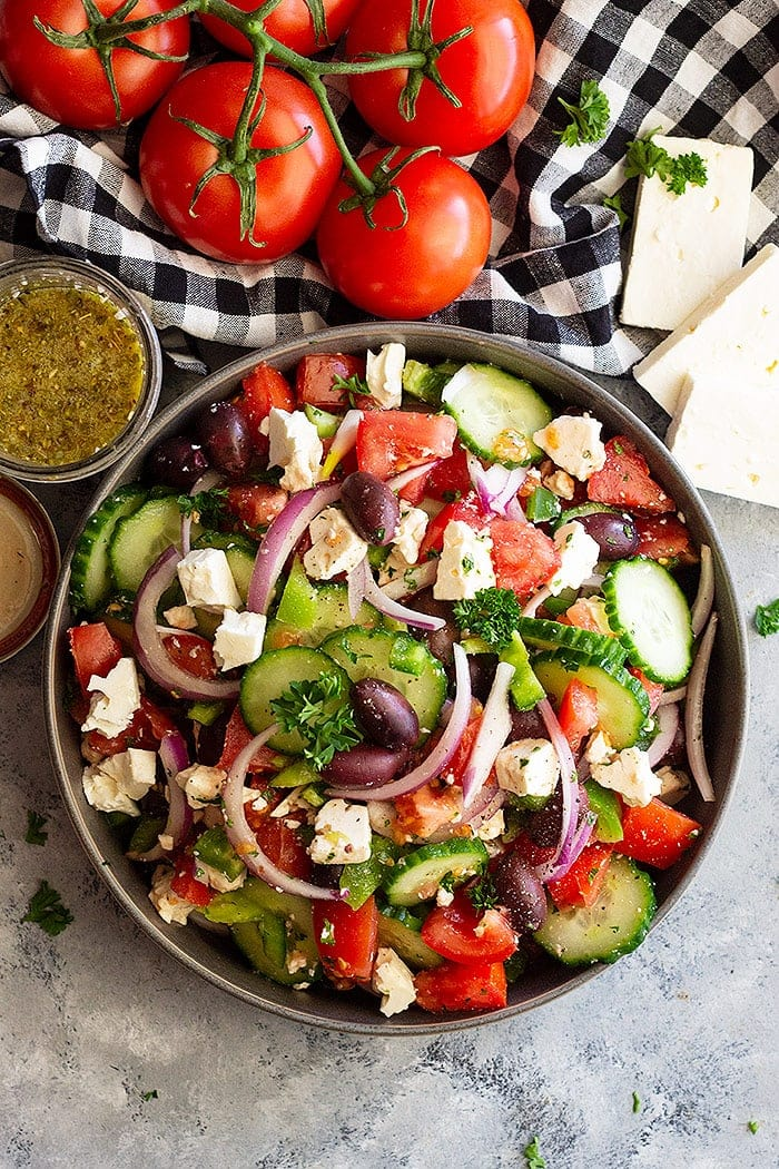 Greek Salad with homemade salad dressing and fresh tomatoes on the side.
