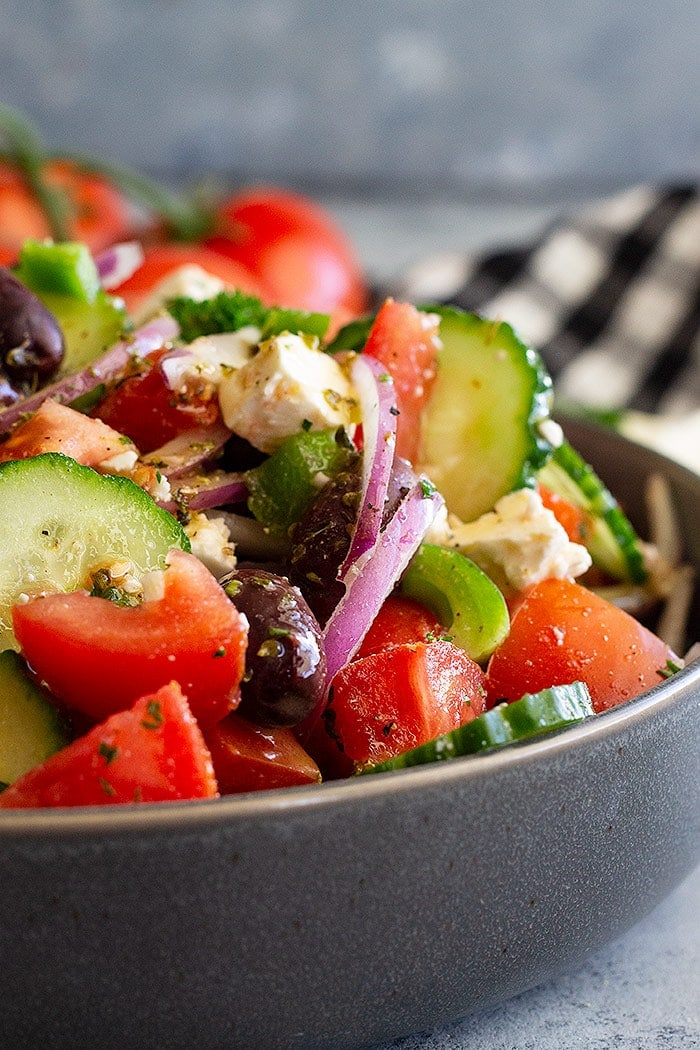 Greek Salad in a gray bowl on a checkered tablecloth.