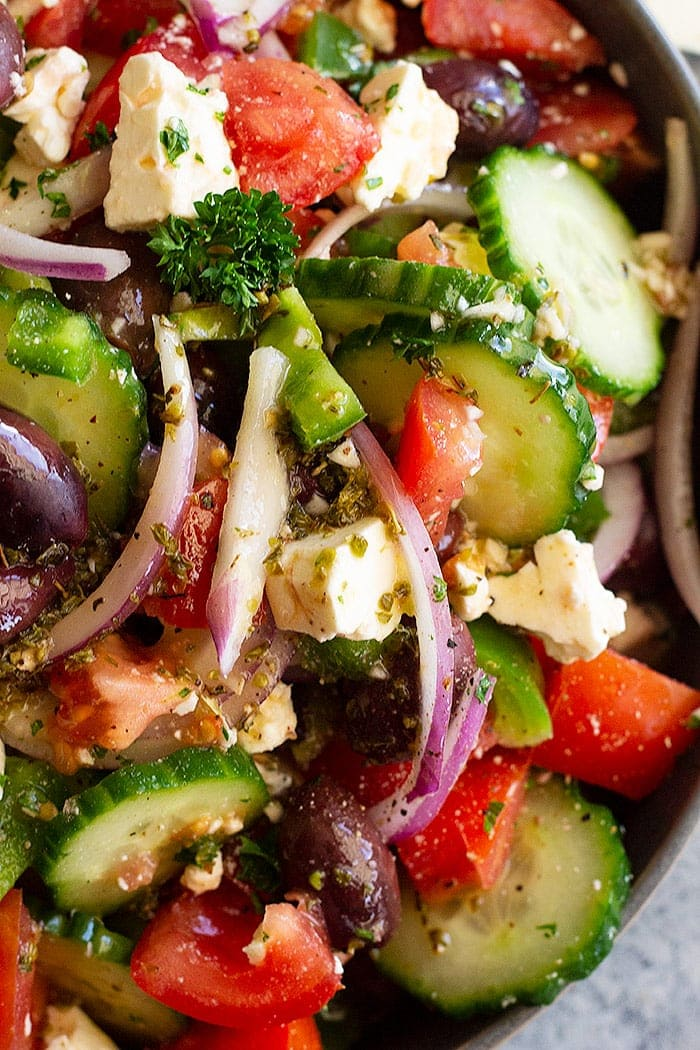 Close of photo of greek salad - packed with cucumbers, feta cheese, red onion, tomatoes and olives.