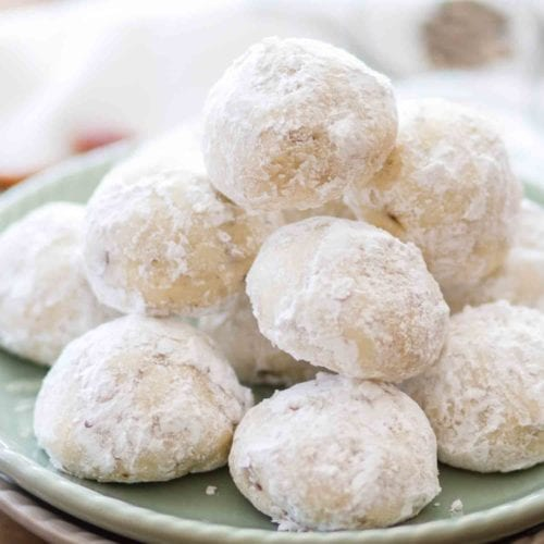 Classic snowball cookies with pecans stacked on a green plate