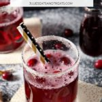 Cranberry mocktail in a glass with sugared rim and two straws