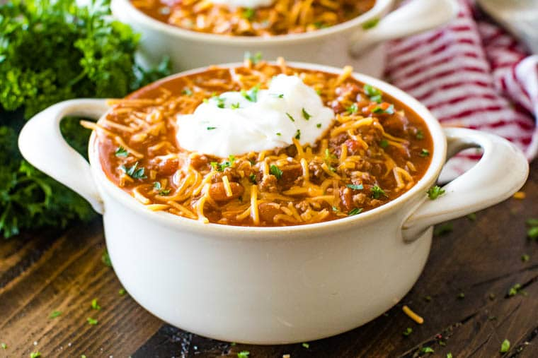 Ceramic bowl of chili topped with shredded cheddar cheese, sour cream and minced parsley.