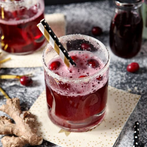 Two Sparkling Ginger Cocktails are shown on a dark background, surrounded by fresh cranberries and ginger