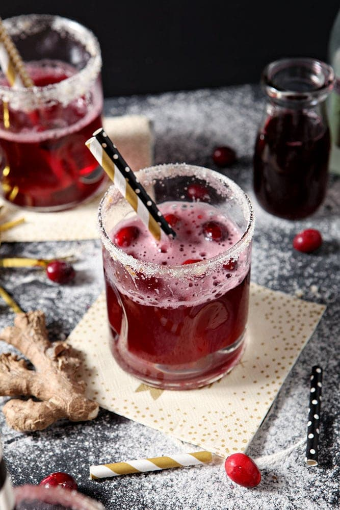 Two Sparkling Cranberry Cocktails are shown on a dark background, surrounded by fresh cranberries and ginger