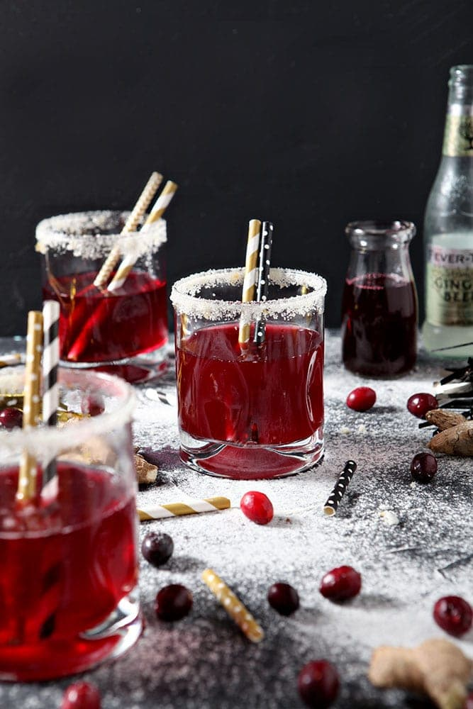Three Sparkling Cranberry Mocktails are served on napkins with golden straws