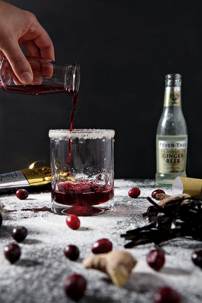 Cranberry juice is poured into a glass to make a Sparkling Cranberry Juice Cocktail