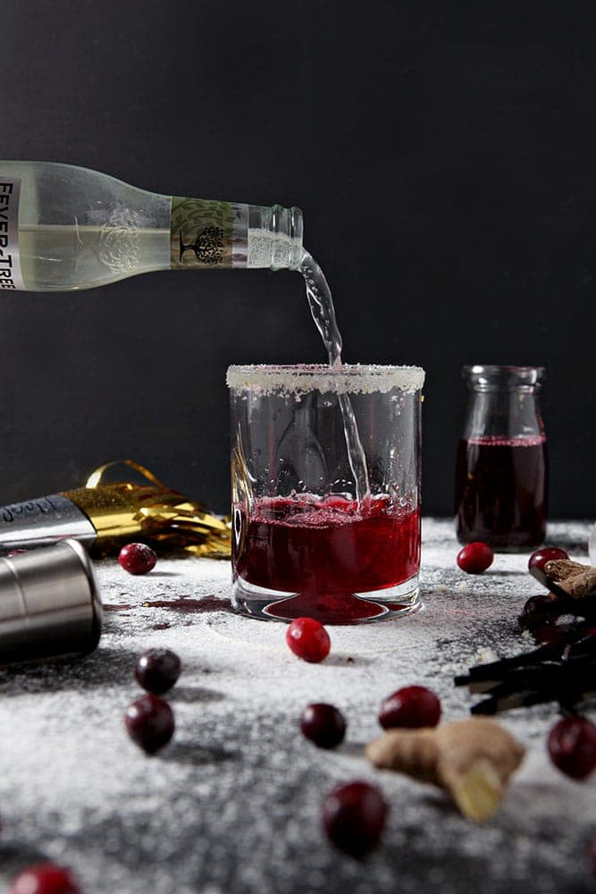 Ginger beer is poured into a glass to make a Sparkling Cranberry Mocktail