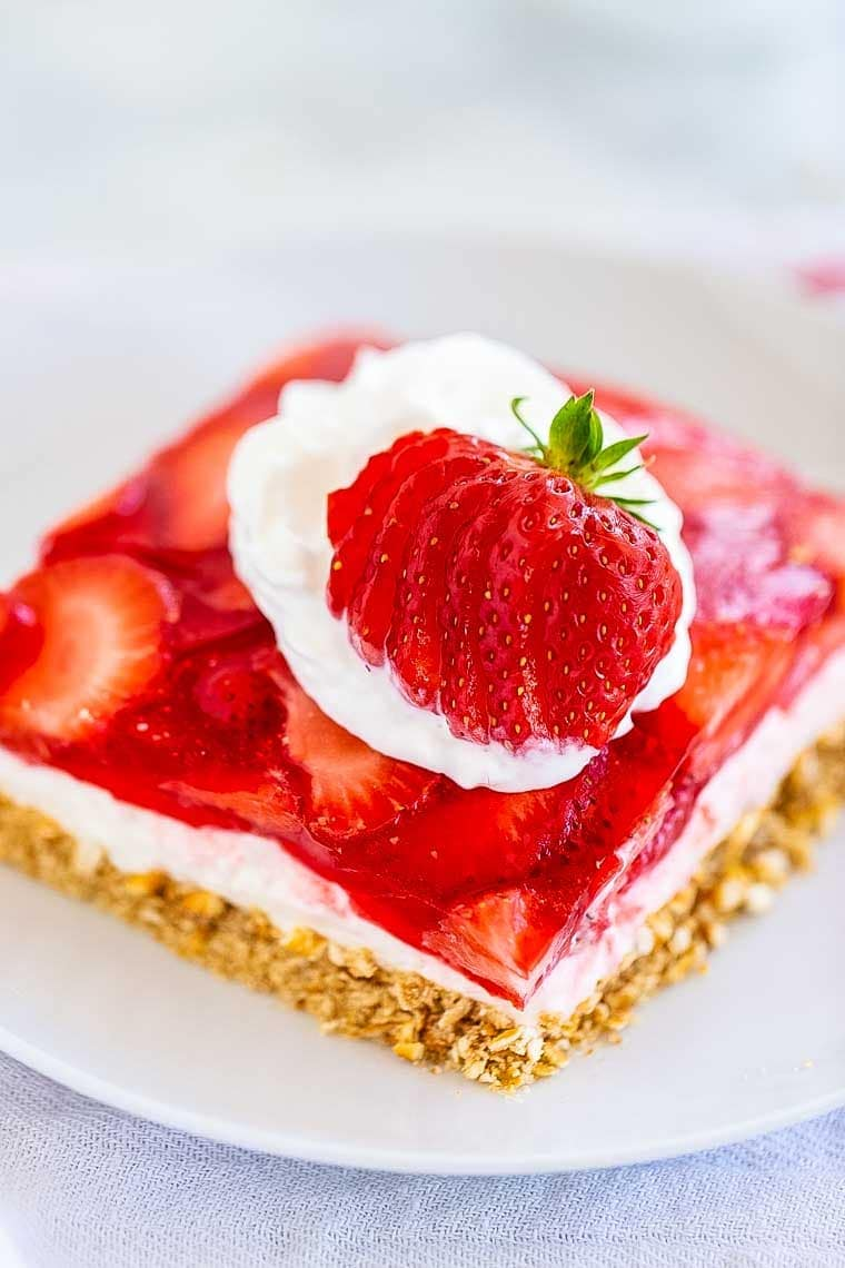 Strawberry Pretzel Salad piece on white plate topped with cool whip and fresh strawberry