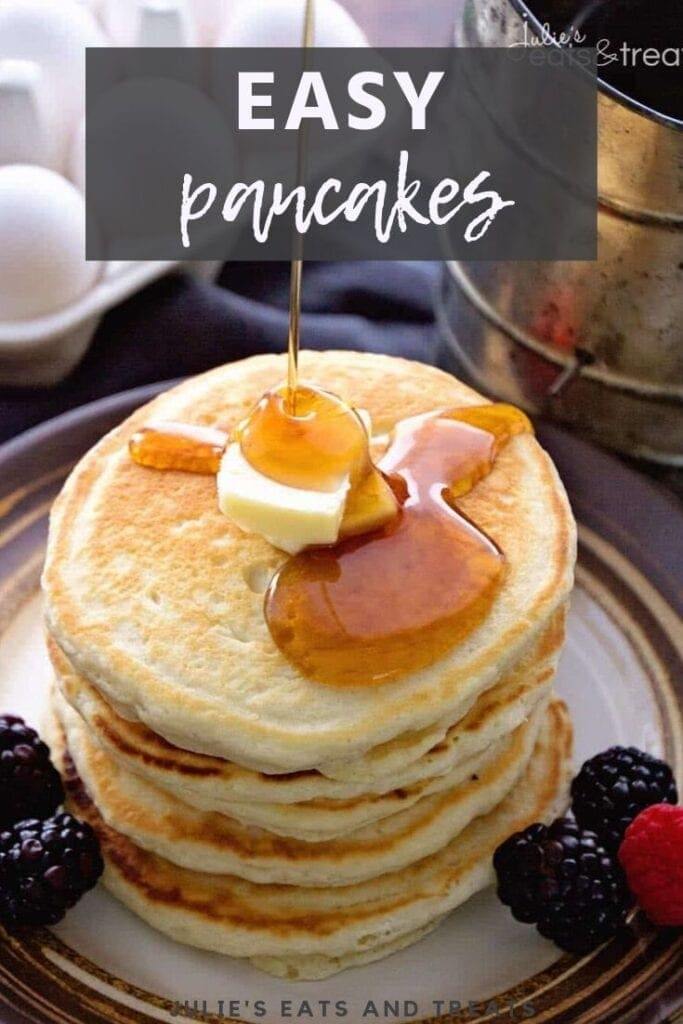 Syrup being poured over a stack of pancakes with butter on top and berries on the side