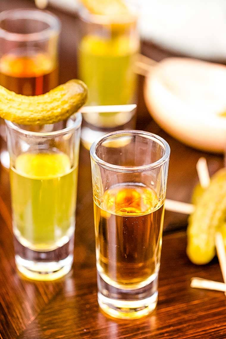 A shot glass filled with whiskey and a shot glass filled with pickle juice topped with a pickle makes a Pickleback Shot