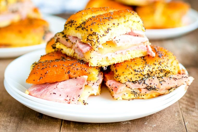 White plate with a stack of baked ham and cheese sliders.
