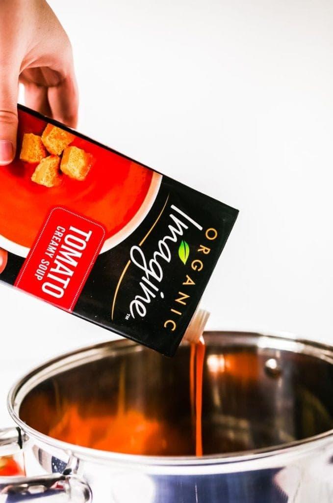 Hand pouring Imagine Tomato soup into pot