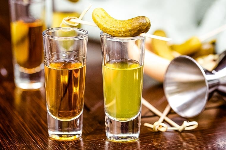 Pickleback Shot topped with a speared dill pickle.