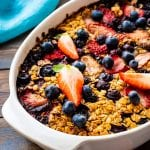 White Baking Dish with Baked Oatmeal topped with strawberries and blueberries on dark wooden background
